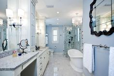 This open, airy master bathroom was transformed from a formerly small, narrow space that also included a small walk-in closet and linen closet. White custom cabinetry and loads of Carrara marble blend with soft gray walls, giving the space an ethereal, spa-like feel. A mix of recessed and decorative lighting add sparkle.