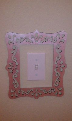super cute (and easy) light switch frame - laser cut unfinished wood frame from Michael's.  1. Three coats of Martha Stewart pearl pink acrylic paint applied w sponge brush.  2. spray on clear coat of matte finish. doesn't affect metallic shine 3. frame around light switch plate and mount to the wall with small strips of mounting tape