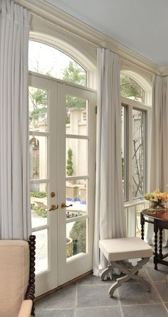 """Drapes can hide a less than appealing view but in this case their subtle color merely """"frames"""" and adds softness. . charisma design Arched Window Curtains, Arch Windows, Arched Doors, French Curtains, White Curtains, Transom Windows, Hallway Curtains, Windows And Doors, Windows Ce"""