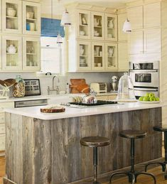 Obsessed with the kitchen island & the glass cabinets. Also note the jug of wine corks.. perfect