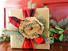 Trendy menswear-inspired red flannel ribbon and a few fresh spigs of greenery give this gift a wintry, woodsy feel. To make the rustic topper, cut a small and medium circle out of upholstery webbing and pull on the outer fibers to create a frayed edge. Use an upholstery needle to stitch the two layers together then sew on a single glass bead. Glue an alligator clip to the back so the topper can be easily clipped onto the gift then later reused by the recipient as a hair or scarf clip.