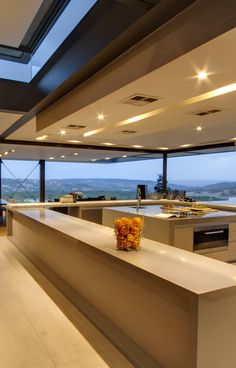 House Boz: The kitchen leads out onto the lanai. When the frameless stacking doors are opened the two spaces become one | Nico van der Meulen Architects