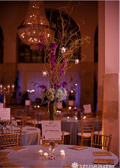 #centerpiece, featuring tall pilsner vase, ringed with blue hydrangeas, filled with tall curly willow branches with purple orchid sprays and candles wired into the branches