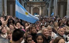 A big group of People in Argentina and what they look like and also the flag that is in the air it the flag for the country Argentina.