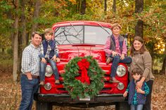 Perfect Christmas family photo. At their home, with their vintage red truck. Love everything about this photo. Fayetteville, Arkansas family photography by Whitney Flora Photography.