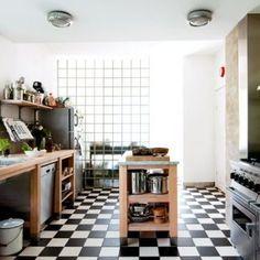cuisine de l'éditeur suédois David Carlson avec mur en pavés de verre qui laisse filtrer la lumière, au centre un billot de préparation, le côté droit regroupe les rangements et les machines et le côté gauche, une cuisinière de pro anglaise Falcon.