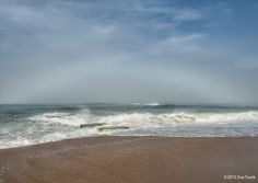 A full fogbow, appearing like an alabaster rainbow over the wild ocean.