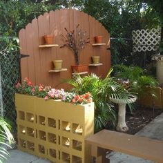 yellow painted cinder blocks - LOVE! Do taller and lots wider for a whole section of garden wall!