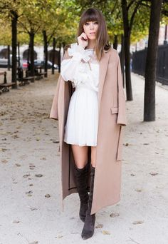 Drape a chic long tan coat over a frilly, feminine white dress, and complete the look with knee high suede boots.