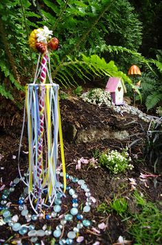 Mini Beltane Pole  If space is an issue take a Dowel or Stick wrap it in colorful ribbon attach a cap for flowers or feathers to be attached and ribbon to dangle down.   on the ground put shiny stones or Glass stones in colorful patterns leave an offering there for The Fay and a note of anything you like the fay to help you with or bless you for the following year