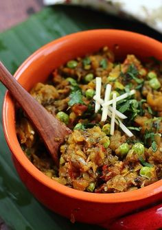 [ Recipe: Spiced Eggplant (Indian) - Vegan - known as Baingan ka Bartha ] Made with: eggplant, onion, tomato, sweet peas, ginger, garlic, chilies, cilantro stalks, cumin seeds, coriander seeds, turmeric powder, oil, salt, and a garnish of cilantro and julienned ginger.  ~ from Akshayapaatram