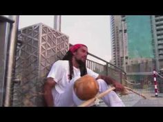 Move sequence @ [58s-1:08s]: Capoeira By Skydive Dubai - Profesoor Garnize ---  (A) armada; (B) esquiva lateral, vingativa; (A) escape, negativa role, meia lua compaco; (B) queda de tres, tesouro de chao. Switch.