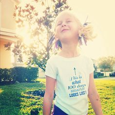 """100th day of school shirt """"this is what 100 days smarter looks like"""", with 100 ribbons in her hair"""