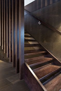 Exposed dark wooden staircase, with basalt tiles and a concrete look wall, create a stylish industrial themed decor