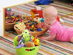 Play space for baby. Low sided baskets, light weight tubs, low shelves secured to wall, mirrors at baby level, hanging fun twirls and swirls from ceiling, soft rug and soft pillows.