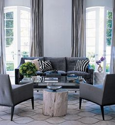 Dovetail gray - Elle Decor. Graphic rug, gray sofa, black & white accents & one pop of color. Natural white wood side table.