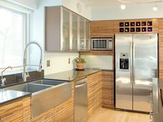 Striking zebra-wood cabinets fill this contemporary kitchen with style. The stainless steel appliances provide striking contrast to the cabinets and are complemented by the apron-front sink and glass-front cabinet door frames.