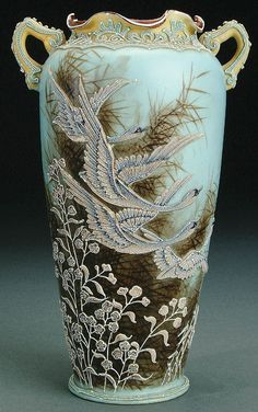 A NIPPON MORIAGE SNOW GEESE DECORATED PORCELAIN HANDLED VASE CIRCA 1915 WITH FOUR MORIAGE GEESE FLYING ABOVE MORIAGE FLOWERS ON A PAINTED RUSHES GROUND