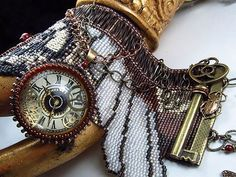 """""""Steampunk on a Loom!""""     STEAMPUNK: Feminine, Strong, Intelligent & Fantastical! The Steampunk culture takes its cues from the Victorian era, while speculating how the world would be different if steam power was the driving force. It has an obsession with time so clock parts are often included, such as gears, old fashion keys and bits of antique metal cast offs. In order to reflect an antique feel, brass, bronze, copper, gunmetal, rich browns, ecru and shades of grey are included."""