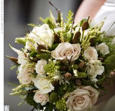 Epitomizing earthy elegance, Erin's lush bouquet contained roses, cattails, pinecones and a wide range of greenery.
