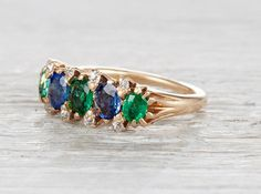 Antique Victorian rose gold five stone ring featuring two natural sapphires weighing approximately one carat total, and three natural emeralds weighing approximately .65 carats total. Accented with eight single cut diamonds.