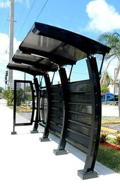 "Prefabricated Cantilever Bus Stop Shelters Troy Metal Buildings (TMB) offers a modern cantilever bus shelter that is custom built to your specifications using 2.5"", 3"" or 4"" custom aluminum extrusions with your option of roof style, finish and color. TMB is dedicated to the use of recyclable materials and alternative energy sources."