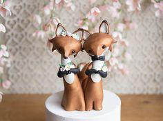 Cette caractéristiques de topper de gâteau de mariage souvenir une paire de renards roux habillé pour leur mariage. La mariée est ornée de fleurs blanches et le marié de sport une boutonnière et un noeud papillon noir.  Je les sculpté à la main avec un mélange personnalisé composé polymère qui a un éclat subtil et persillage. Leurs yeux sont des perles en cristal Swarovski et ils se tiennent juste sous 5-pouces de haut.  Vous recevrez la même sculpture exactement comme on le voit sur les…