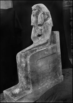 Exploration of the stepped pyramid complex of Djoser. (1924-1935)..The famous limestone statue of Djoser, star attraction of the Cairo Museum, suddenly loomed out of the desert sands during the winter of 1925, at the foot of the north face. Cecil Firth had the piece photographed on a black ground. The king was represented at the end of his reign wearing a white coat, his waist encircled by a bull's tail, seated on the throne of the two Egypts.....CHADOUF MOHAMMED/COLLECTION PATRICK…