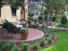 Round brick patio, landscape filling in curvatures with adjacent walkways.