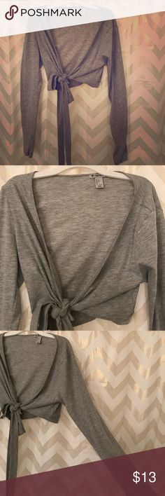 """Grey yoga wrap """"crop"""" shirt Forever 21 brand. Super cute! Worn one time only. Found out the hard way that I don't like to lift weights in long sleeves. The slit on each sleeve at the bottom is suppose to be for your thumbs. I guess it's a yoga thing. Forever 21 Tops Crop Tops"""