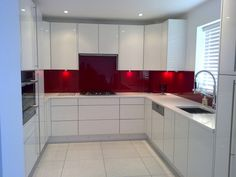 red splashback kitchen - nice clean lines on drawers with no handles