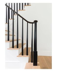 Beautiful contrast of black spindle/ rail and post, along with painted risers and hardwood treads. Love!