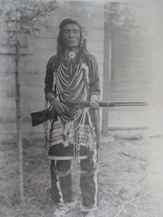 Atimoyoo, A Cree man armed with a lever action repeating rifle in traditional dress, circa 1905 | Saskatchewan Archives Board S-B6777