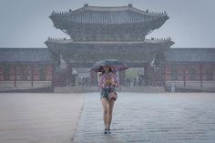 Uma mulher caminha em frente ao palácio Gyeongbokgung em Seul, na Coreia do Sul. O país passa pela temporada anual de chuvas, que vai do fim de junho até o final de julho (Foto: Ed Jones/AFP)