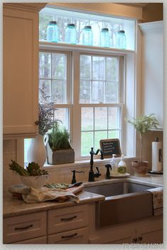 I love everything about this...the huge sink, the faucet, the hardware on the cupboards and drawers, the countertop, and the mason jars at the top of the window. I want this!