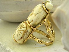 This massive ring is stunning...the little ivory child is carved in great detail and is signed .I believe it is a bead,there are small holes top and bottom.Even the back is carved intricately.Very old and beautiful.The 14k gold band is at least a size 10,it is 1 inch wide...The gold is all done in gorgeous bamboo.the whole ring weighs 35,3 grms on my scale.the ivory carving is 2 inches