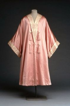 """Evening coat by Liberty & Co, 1900-25 London, the Museum of Fine Arts, Boston  Pink satin evening coat or wrap, cut in kimono style; collar and cuffs of white satin embroidered with pink silk in conventionalized floral design; lined with white satin. Front trimmed with white satin buttons wrapped with pink thread and pink tassels. Label: """"Liberty and Co., London and Paris"""""""