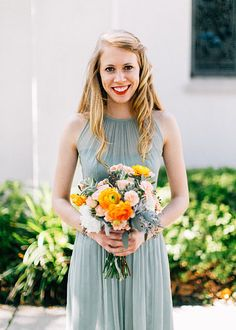 a spring bridesmaid's bouquet of loosely arranged peach and orange ranunculus, spray roses, peach roses, dusty miller and seeded eucalyptus.
