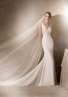 Delicate mermaid style wedding dress in crepe, with Chantilly and lace work on the bodice. A V-neckline and lace details over the hips make this a fabulously feminine design. The Knot provides price estimates to give you a general idea of the cost of a dress. Please visit retailers in your area for exact pricing. Prices will vary by region.