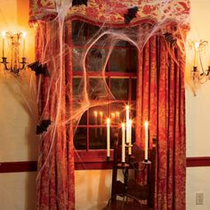 Halloween Wicked Window ~   Use candlelight to create dark shadows in the corners. Here, the ghostly white tapers in a flea market candelabra enhance the creepiness of cobwebs and flying bats.