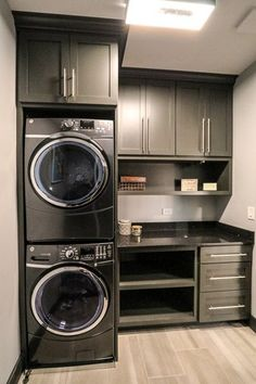 Second floor laundry room with custom built and grey painted cabinetry surrounding stacked washer and dryer.