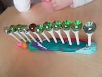 golf tees in playdough, balancing marbles on top