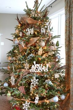Love this tree with burlap ribbon, grapevine, floral accents and simple ornaments.