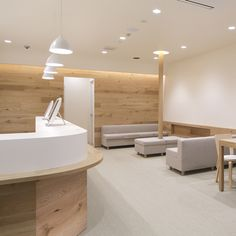 Pale oak walls and muted furnishings create a calming environment for patients inside this dispensing pharmacy in Tokyo by Hiroyuki Ogawa Architects.