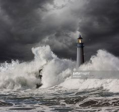 A lighthouse keeper is vigilant atop a lighthouse as waves crash against the structure in an ocean storm.