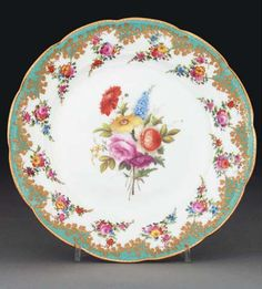 A Nantgarw (London-decorated) plate CIRCA 1820, IMPRESSED NANT-GARW/C.W. MARK Painted with a bouquet to the centre, within turquoise borders suspending trailing garlands within raised-gilt trailing roses 9 1/8 in. (23.2 cm.) wide