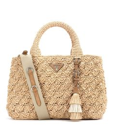 Prada - Rafia tote - Crafted from textured rafia, Prada's beige-hued tote is the ideal companion for long summer days thanks to its simple silhouette and poolside-friendly exterior. A suede plaque with the designer's name sits on the front for recognisable charm. On busy days, a removable canvas strap can be used to convert this into a hands-free style. seen @ www.mytheresa.com