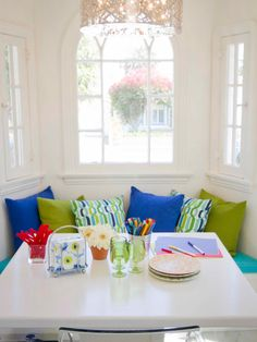 A bench built into a bay window sits behind a contemporary white table to create a charming eating nook that's not only functional but a fun pop of color in this white galley kitchen.