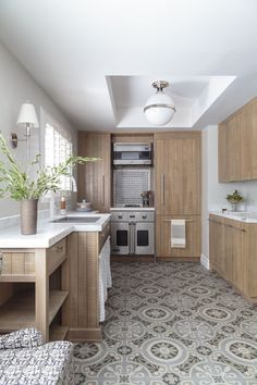 Rustic charm reigns in this calm kitchen from Bronwyn Poole by Touch Interiors. A tile backsplash and complementary flooring tempers the modern space with a sense of coziness.