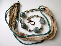 Taiga - crusty white and aqua lampwork glass, pale blue Indonesian recycled glass beads, and beige & teal recycled sari silk ribbon necklace. $68.00, via Etsy.